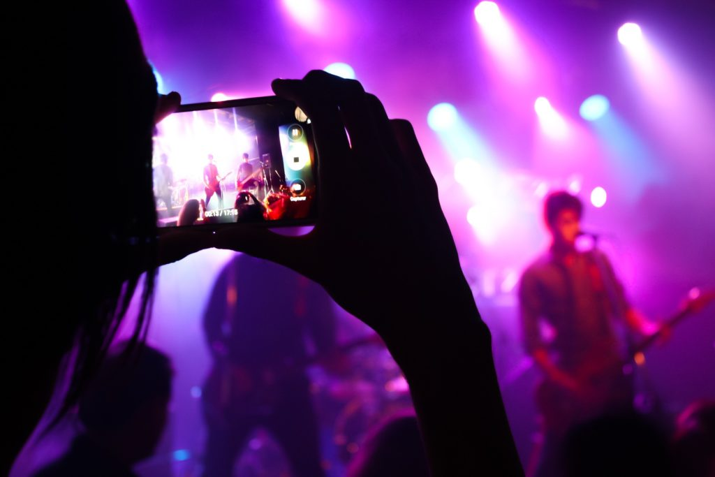 Spectator uses smartphone to take photo of musicians on the state.